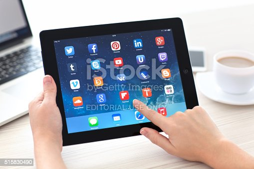 istock Woman holding iPad with social media app on the screen 515830490