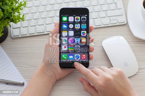 istock Woman holding iPhone 6 Space Gray over the table 468884206