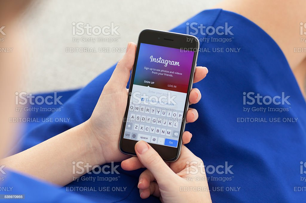 Woman holding iPhone 6 Space Gray with Instagram stock photo