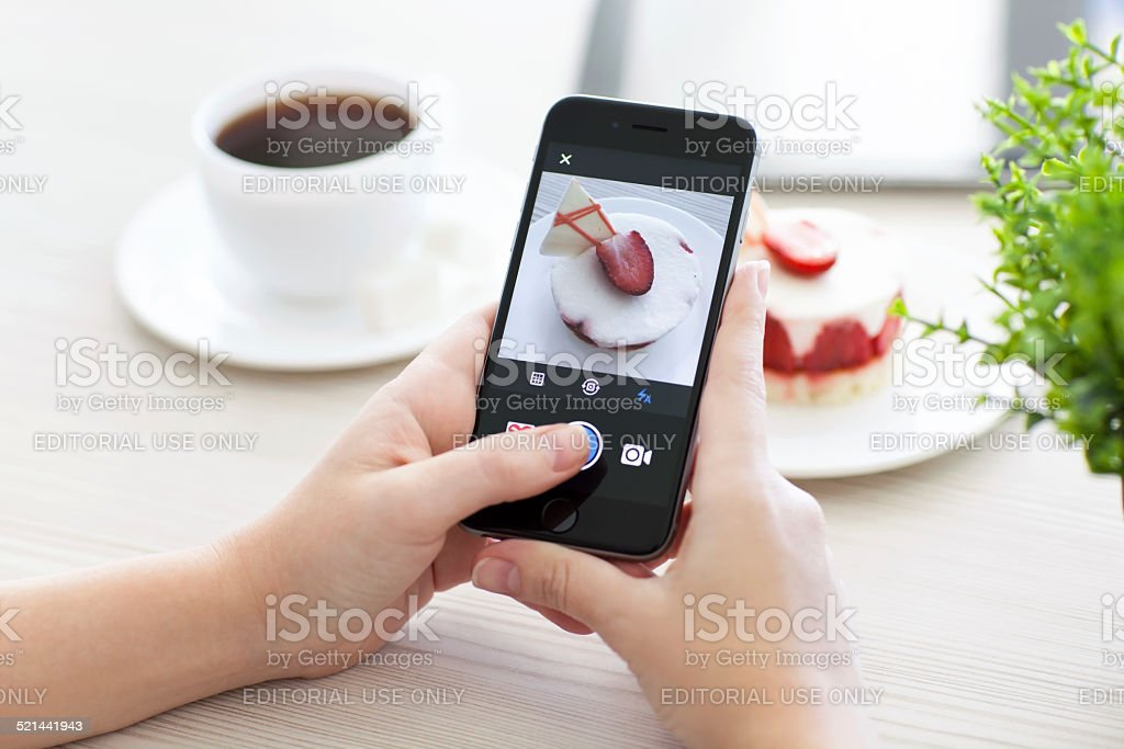 Woman holding iPhone 6 Space Gray with service Instagram stock photo