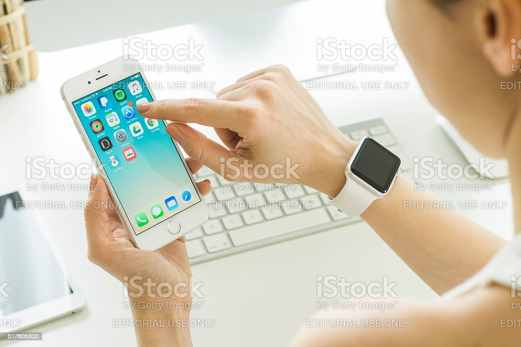 Woman Holding iPhone 6s Over the Table stock photo