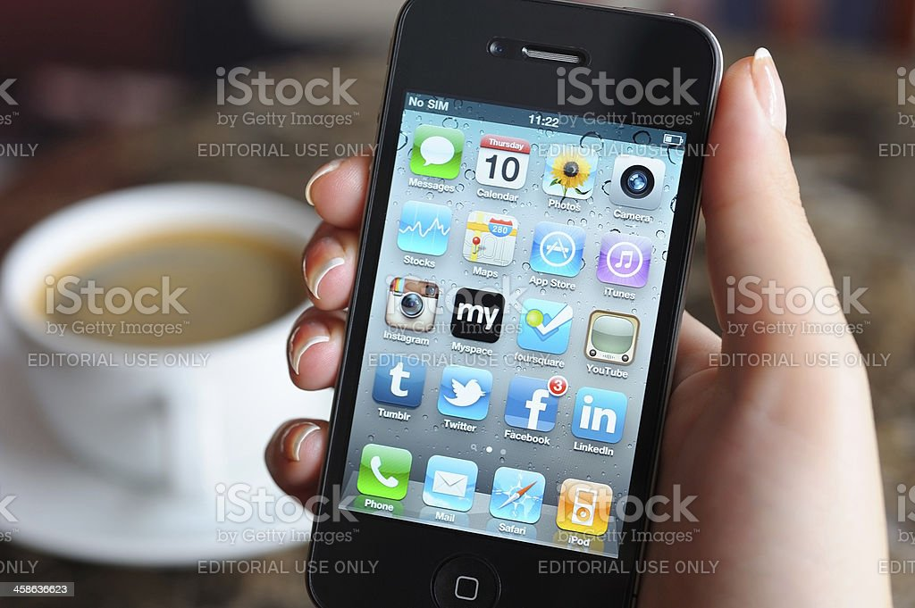 Woman holding iPhone in a coffee shop stock photo