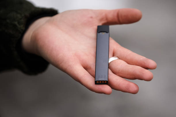 Woman holding Juul e-cig A woman is holding a Juul e-cigarette, in Montreal. electronic cigarette stock pictures, royalty-free photos & images