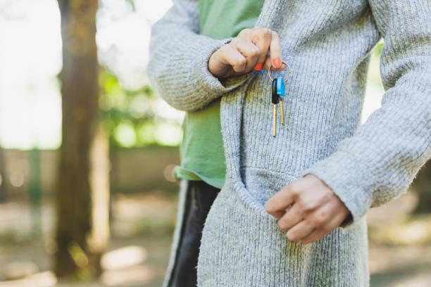Woman holding keys above the pocket stock photo