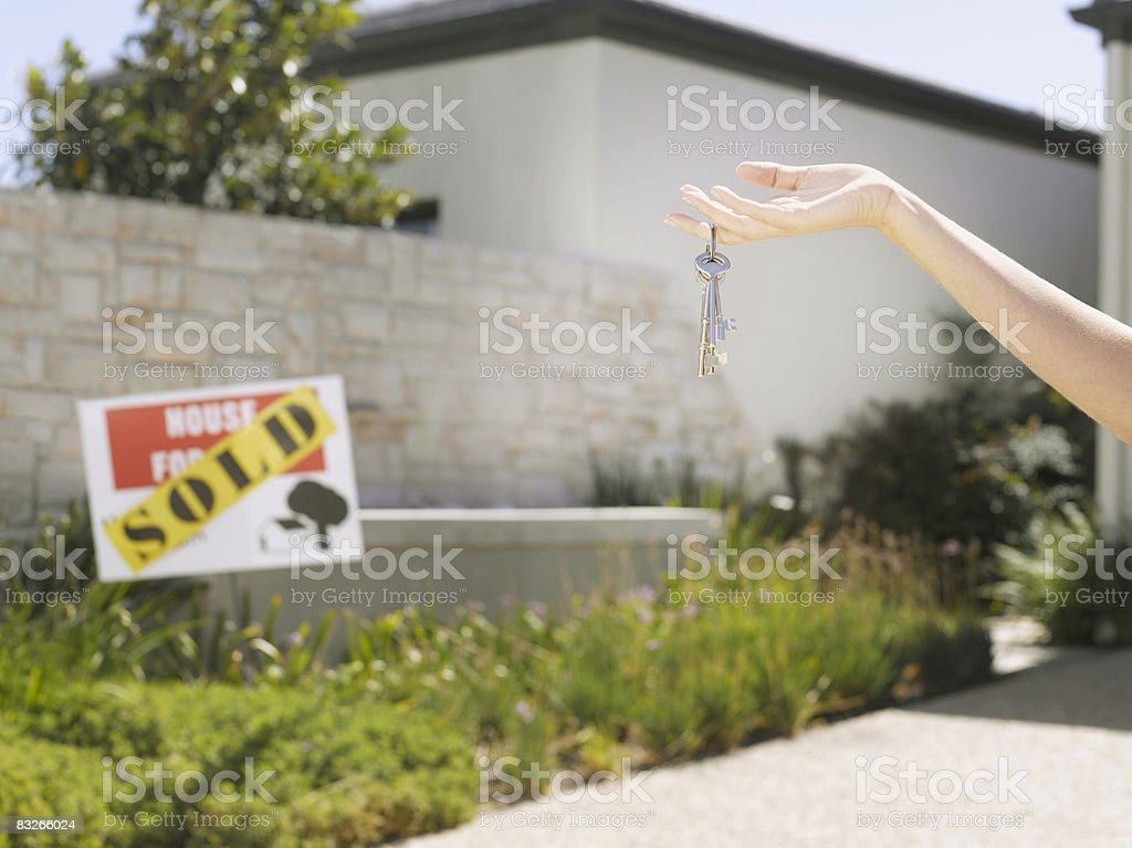 Woman holding keys to new home royalty-free stock photo