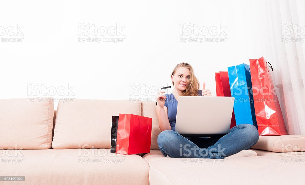 Woman holding laptop and card showing like stock photo