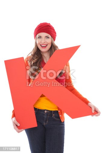 Attractive woman in autumn clothes holding big 3D letter K and smiling at camera. Isolated on white. People with letters and numbers concept. Look for other images from this series. Click on image below for lightbox.