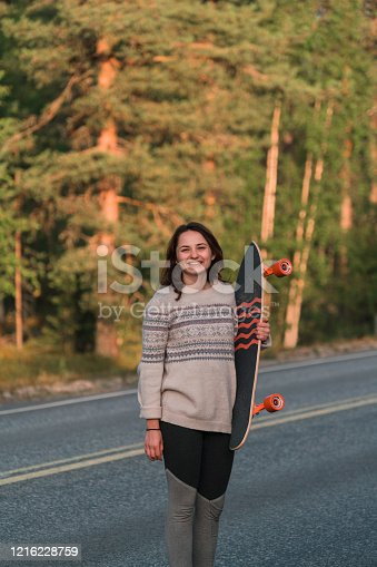 Young Caucasian woman looking at camera while  holding longboard  on the road in Finland
