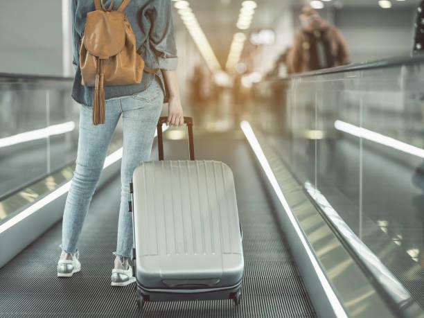 woman holding luggage on moving stairs - donna valigia solitudine foto e immagini stock