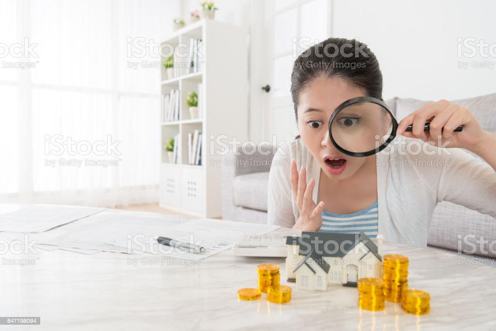 mulher segurando a lupa, olhando para a pilha de moedas de ouro - foto de acervo