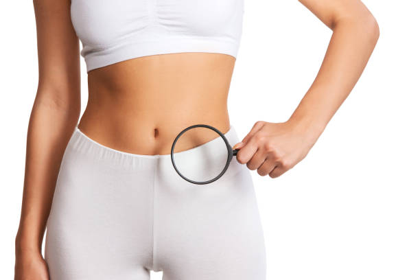 Woman holding magnifying glass over her abdomen stock photo