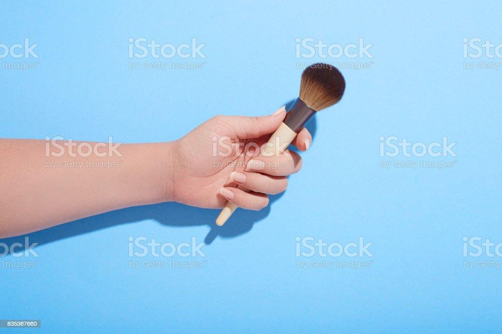 Mujer que sostiene el pincel de maquillaje en la mano sobre fondo azul - foto de stock