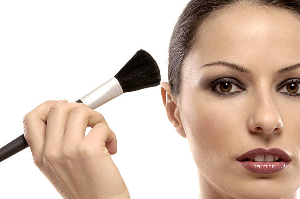woman holding make-up brush in her hand stock photo