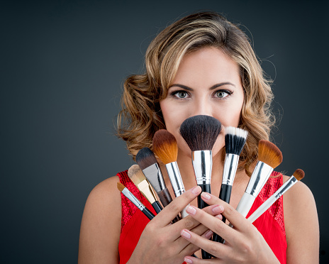 woman holding makeup brushes stock photo  download image