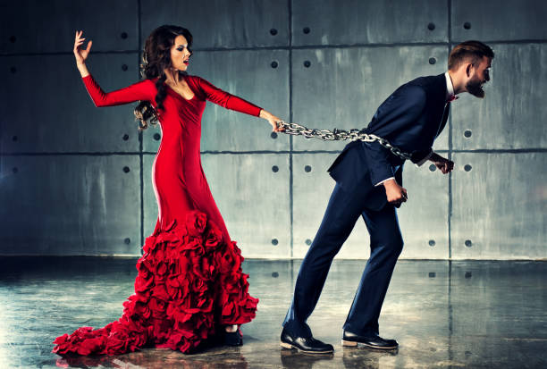 Woman holding man on heavy chain stock photo