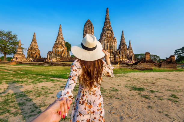Woman holding man's hand and leading him to Ayutthaya Historical Park, Wat Chaiwatthanaram Buddhist temple in Thailand. stock photo