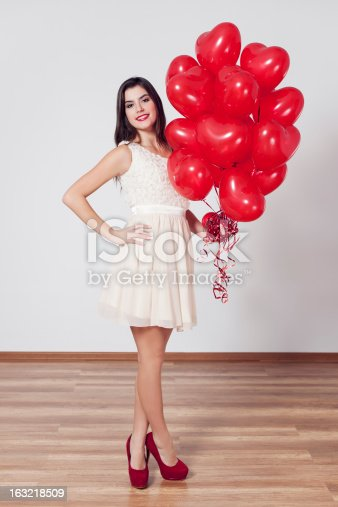 579443552istockphoto Woman holding many balloons in heart-shaped 163218509