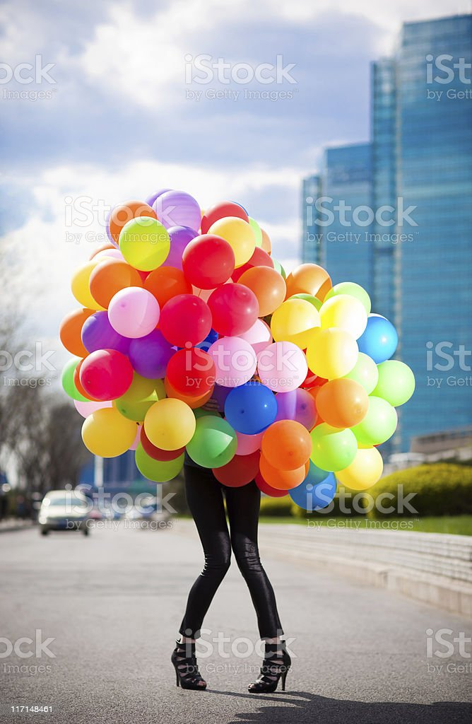 Woman holding many balloons stock photo