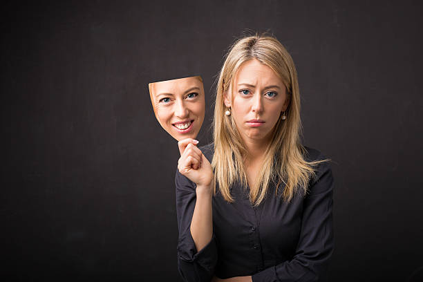 woman holding mask of her happy face - mask disguise stock photos and pictures