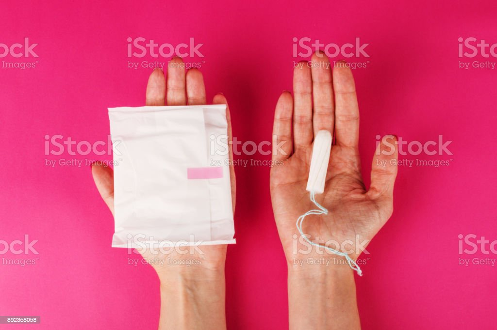 Woman holding menstrual tampon on a pink background. Menstruation time. Hygiene and protection stock photo