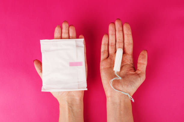 Woman holding menstrual tampon on a pink background. Menstruation time. Hygiene and protection