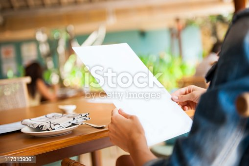 Close up photo of woman holding menu in the restaurant, selective focus