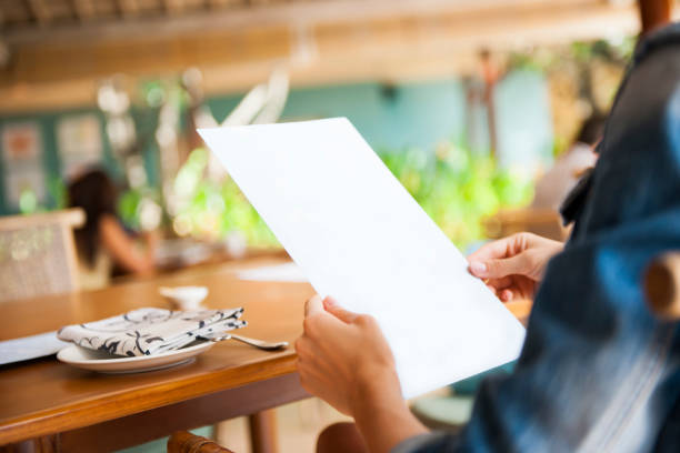 Woman holding menu in the restaurant stock photo
