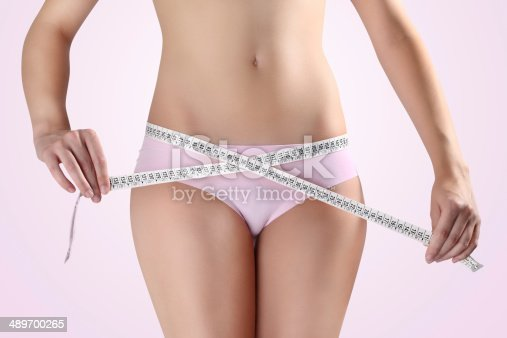 1163494373 istock photo woman holding meter with hands near waistline, on a pink 489700265