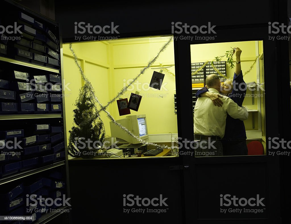 Woman holding mistletoe and hugging man in office royalty-free stock photo