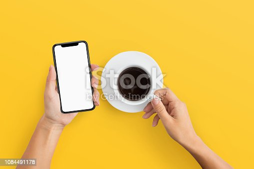 1084491176 istock photo Woman holding mobile phone and coffee cup 1084491178