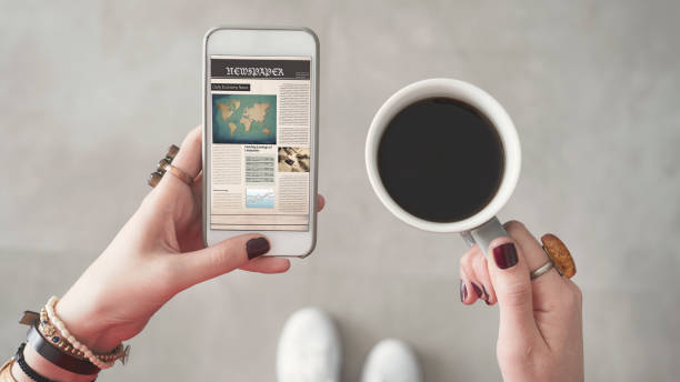 Woman holding mobile phone and reading news from screen other hand holding coffee cup stock photo