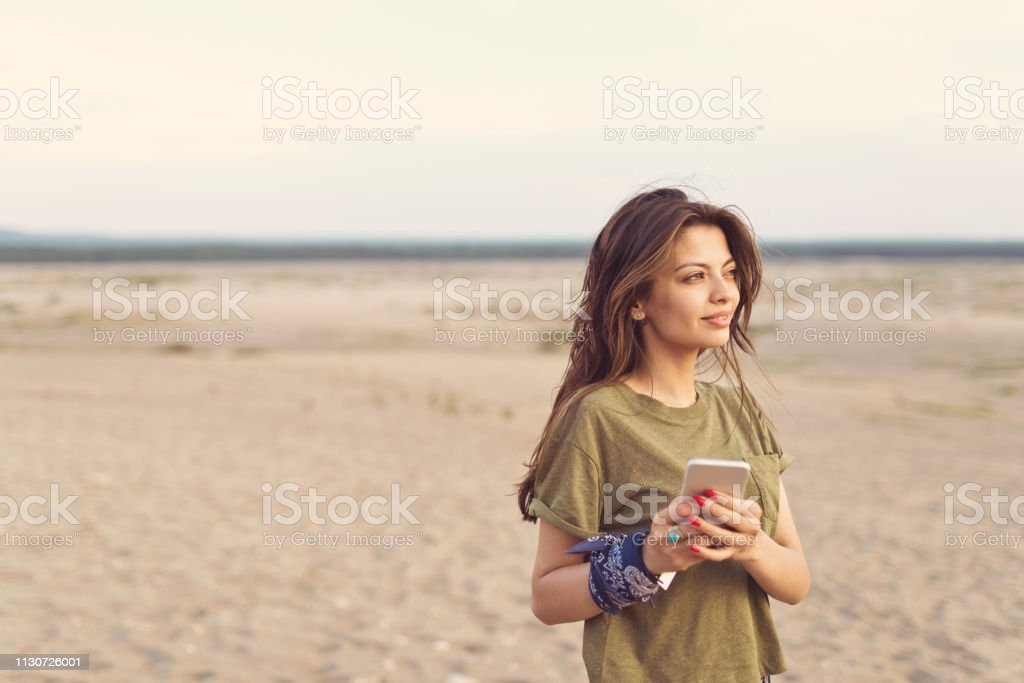 Woman holding mobile phone in desert Young woman holding mobile phone in desert. Hiker is smiling while looking away. She is enjoying her summer vacation on sandy landscape. 25-29 Years Stock Photo
