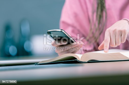 Close up view of woman holding mobile phone while reading book