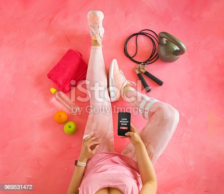 istock Woman holding mobile phone with fitness app ready for weight loss training. 969531472