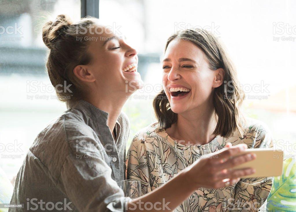Donna con telefono cellulare con freind, ridendo - foto stock