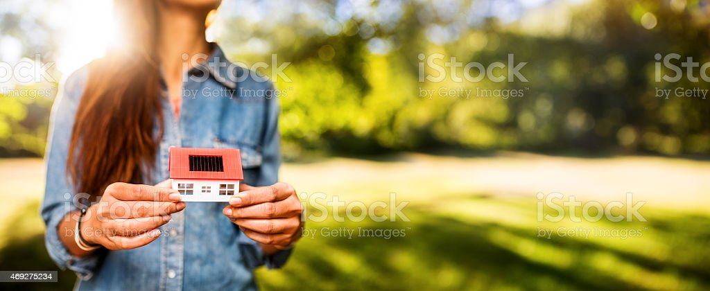 Woman holding model of new home on a sunny lawn stock photo