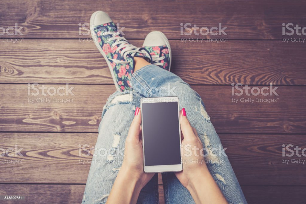 Woman holding modern white smart phone with black empty screen over wooden floor royalty-free stock photo