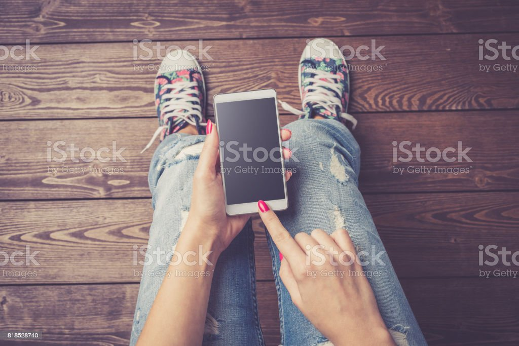 Woman holding modern white smart phone with black empty screen over wooden floor stock photo