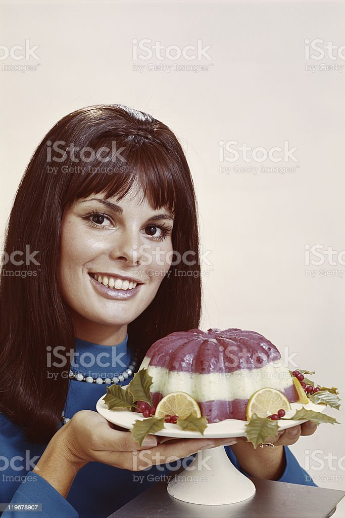 Woman holding mousse against white background, close-up, portrait stock photo