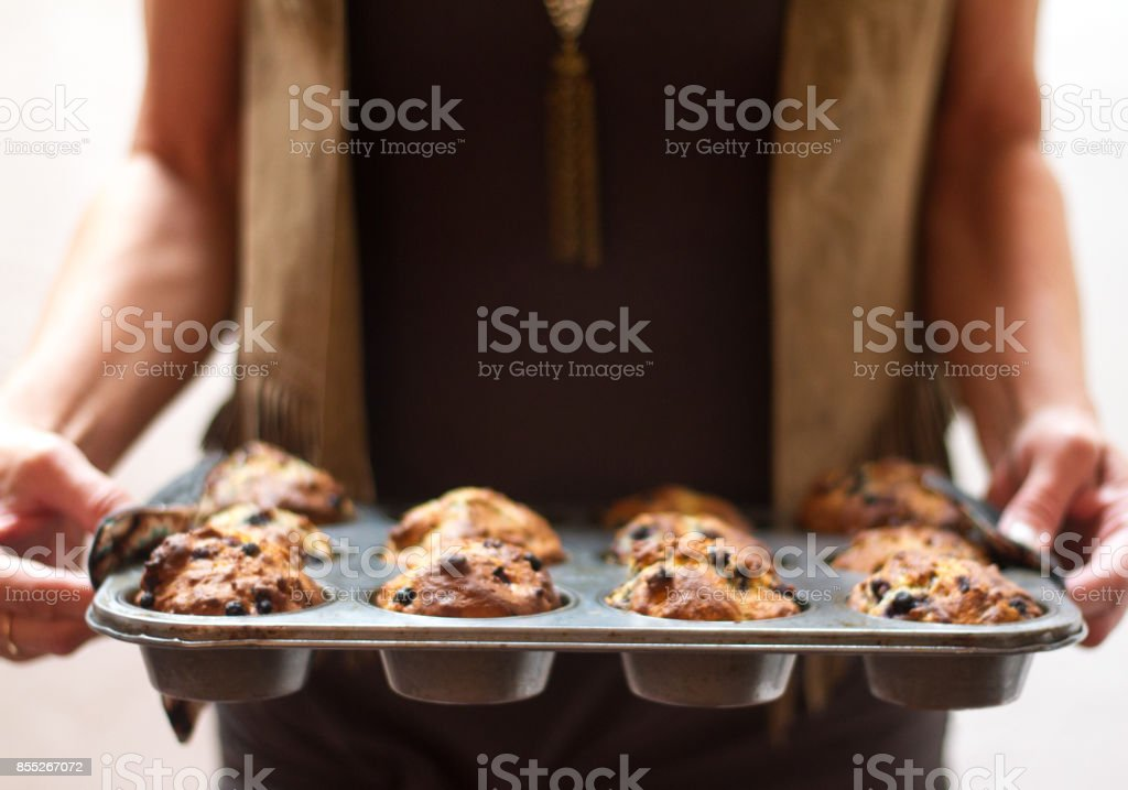 Woman Holding Muffin Tin of 12 Blueberry Muffins (Close-Up) stock photo