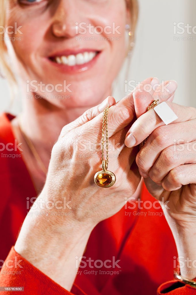 Woman holding necklace in jewelry store stock photo