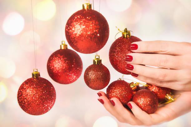 frau hält neue jahr runde kugeln - nageldesign weihnachten stock-fotos und bilder