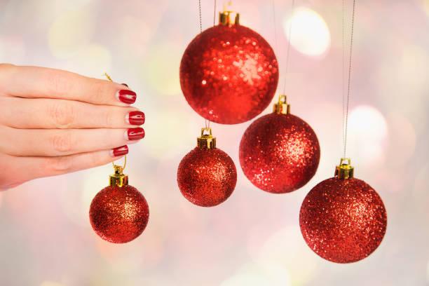 frau holding neue ganzjährig kugeln bereit, baum schmücken - nageldesign weihnachten stock-fotos und bilder