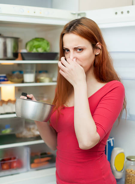 woman  holding  nose because of bad smell woman  holding  nose because of bad smell near fridge at home addle stock pictures, royalty-free photos & images