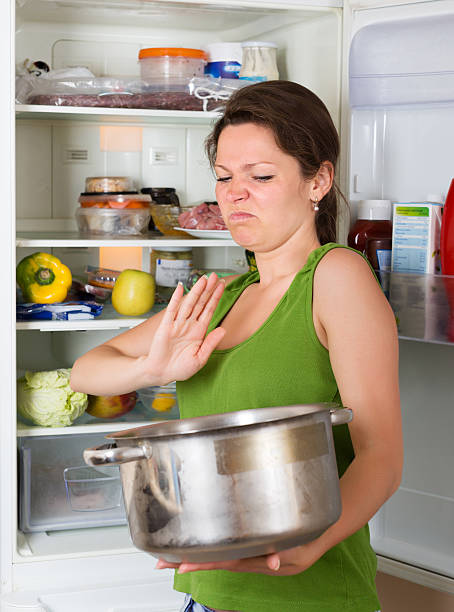 Woman holding nose near refrigerator Woman holding her nose because of bad smell from food near refrigerator  at home addle stock pictures, royalty-free photos & images