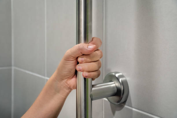 Woman holding on handrail in toilet. stock photo
