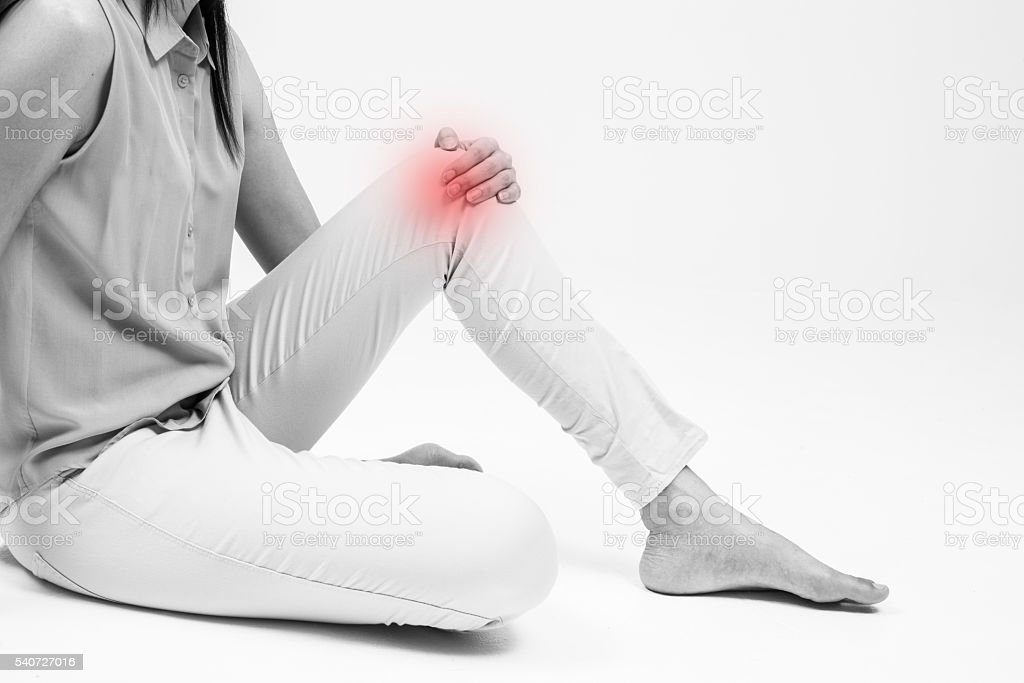 Woman holding on sore knee isolated on white. stock photo