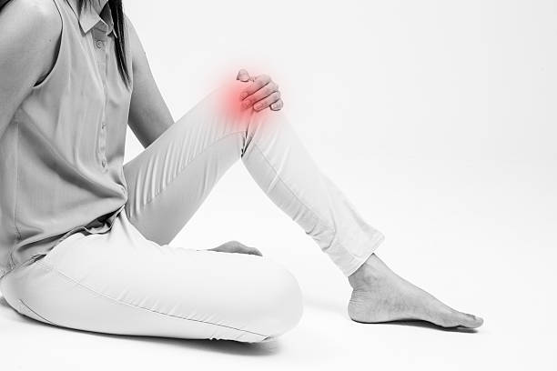 woman holding on sore knee isolated on white. - knuckle stock photos and pictures