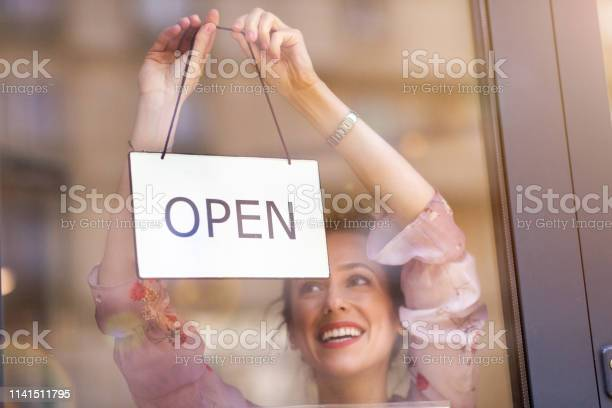 Woman holding open sign in cafe picture id1141511795?b=1&k=6&m=1141511795&s=612x612&h=gyagufzi1hwmvglo323gu8e9 dablxnbjzi jjsy7h8=