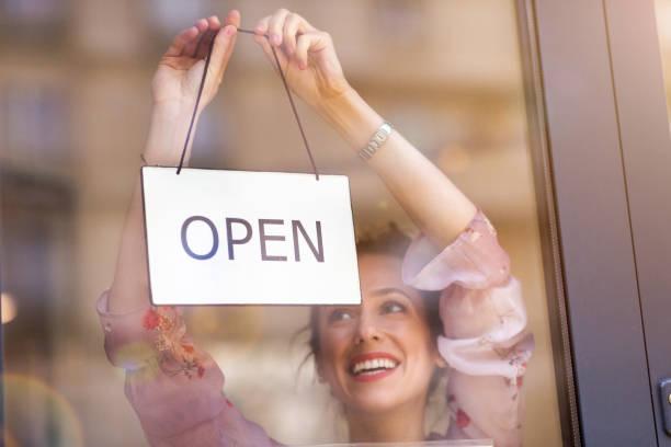 Frau hält offenes Schild in Café – Foto